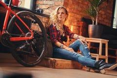 Sinnliches blondes Hippie-Mädchen mit dem langen gelockten Haar kleidete in einem Vlieshemd und -jeans an, die auf einer Holzkist Lizenzfreie Stockbilder