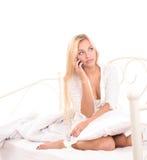 Sinnliches blondes Mädchen, das am Telefon im Bett spricht Stockbild