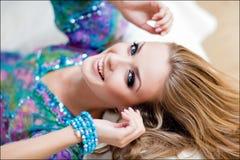 Sinnliches blondes Mädchen mit blauen Augen in einem blauen Kleid, das auf liegt Lizenzfreie Stockfotos