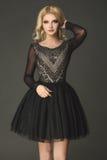 Sinnliches, blondes Modell, das schwarzes Kleid mit weißem Muster trägt Stockbilder