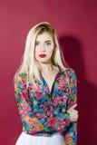 Sinnliches blondes Modell mit dem langen Haar im bunten Hemd betrachtet die Kamera auf rosa Hintergrund Hübsches Mädchen mit Stockbild