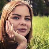 Sinnliches junges blondes auf dem Gras draußen liegen Lizenzfreie Stockbilder