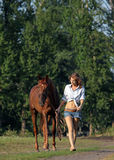 Sinnliches junges Schönheitsbauernmädchen geht mit Pferd Stockbilder