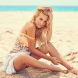 Sinnliches Mädchen, das auf sandigem Strand sitzt Lizenzfreie Stockfotos