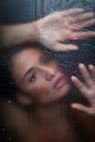 Sinnliches Mädchen hinter dem Glas Stockfoto