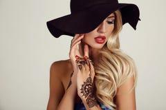 Sinnliches Mädchen im eleganten schwarzen Hut mit mehendi Muster auf Händen Lizenzfreies Stockbild