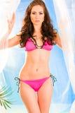Sinnliches Mädchen im rosafarbenen Bikini, der auf Strand aufwirft. Lizenzfreie Stockfotos