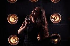 Sinnliches Porträt der herrlichen Frau im gedämpften Licht, das einen Rand von hält stockbild