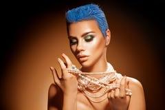Sinnliches Porträt der jungen Frau mit Perlen schließen blaue Frisur kurz Stockfoto