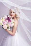 Sinnliches portrat der jungen schönen Braut, die Blumenblumenstrauß hält Lizenzfreie Stockfotos