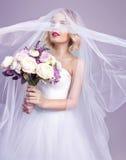 Sinnliches portrat der jungen schönen Braut, die Blumenblumenstrauß hält Stockfotos