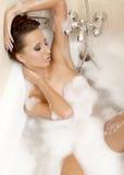 Sinnliches reizvolles Mädchen, das im Badschaumgummi sich entspannt Stockbilder
