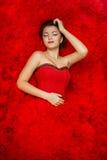 Sinnliches schönes Mädchen liegt auf einem Hintergrund des roten Kleides Stockfotos