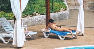 Sinnlig avslappnande near simbassäng för ung kvinna lager videofilmer