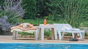 Sinnlig avslappnande near simbassäng för ung kvinna arkivfilmer