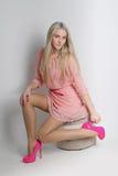 Sinnlig blond kvinna med skinande lockigt silkeslent hår i eleganta dres royaltyfri fotografi