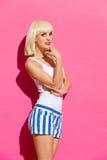 Sinnlig blond kvinna på rosa bakgrund Fotografering för Bildbyråer