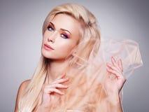 Sinnlig blond kvinnabeläggning vid beige tyg Royaltyfri Bild