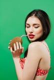 Sinnlig brunett med den tropiska coctailen i händer som poserar på grön bakgrund arkivbilder