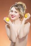 Sinnlig Caucasian blond flicka som poserar med två citroner i händer Lyft räcker Royaltyfria Bilder