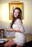 Sinnlig elegant ung kvinna i den vita klänningen som rymmer ett vinexponeringsglas Arkivfoto