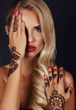 Sinnlig flicka med blont hår med mehendimodellen på händer arkivfoto