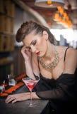 Sinnlig flicka med ursnyggt decolletagesammanträde som drömmer på stången med en drink Härlig flicka med den ursnygga kroppen med Arkivfoton