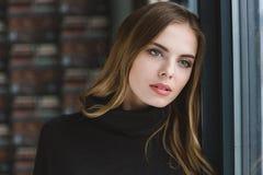 Sinnlig fundersam ung kvinnlig som drömmer nära fönstret Royaltyfria Foton