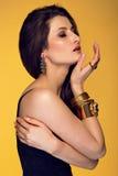 Sinnlig härlig brunettkvinna som poserar i svart klänning och guld Arkivfoto