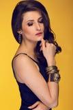 Sinnlig härlig brunettkvinna som poserar i svart klänning och guld Arkivbilder