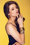 Sinnlig härlig brunettkvinna som poserar i svart klänning och guld Royaltyfri Foto
