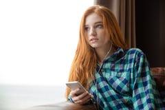 Sinnlig härlig ung kvinna som lyssnar till musik och bort ser royaltyfri bild