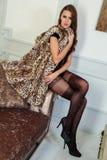 Sinnlig kvinna för brunett som poserar på en soffa som bär den svarta sexiga damunderkläderbodysuiten och lyxpälslaget Arkivbild