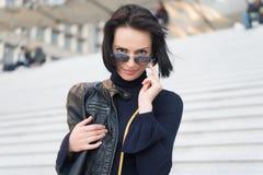 Sinnlig kvinna i solglasögon på trappa i paris, Frankrike, skönhet Kvinna med brunetthår i svartkläder, mode Ambition som är chal arkivfoton