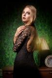 Sinnlig kvinna i svart klänning på grön tappninginre arkivfoto