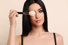 Sinnlig kvinna med den långa hållande yrkesmässiga makeupborsten för mörkt hår Royaltyfri Foto