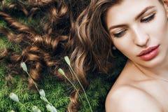 Sinnlig kvinna med långt hår som ligger på vårgräs royaltyfri foto