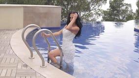Sinnlig kvinna med mörkt hår i den lyxiga bröllopsklänningen som poserar nära simbassäng