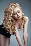 Sinnlig kvinna med skinande lockigt långt blont hår Arkivbild