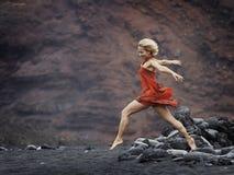 Sinnlig kvinna som poserar på den vulkaniska stranden i sommar Arkivfoton