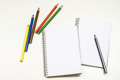 Sinnlig sketchbook och färgpennor på en vit tabell Vit tabell och Royaltyfri Fotografi
