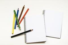 Sinnlig sketchbook och färgpennor på en vit tabell Vit tabell och Arkivfoton