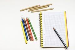 Sinnlig sketchbook och färgpennor på en vit tabell Vit tabell och Arkivbild