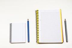 Sinnlig sketchbook och färgpennor på en vit tabell Vit tabell och Arkivfoto