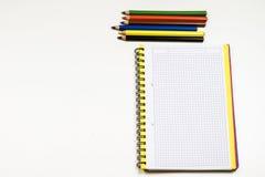 Sinnlig sketchbook och färgpennor på en vit tabell Vit tabell och Fotografering för Bildbyråer