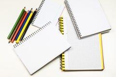Sinnlig sketchbook och färgpennor på en vit tabell Vit tabell och Arkivbilder