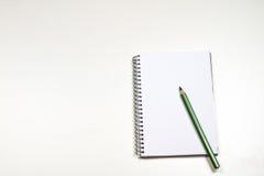 Sinnlig sketchbook och färgpennor på en vit tabell Vit tabell och Royaltyfri Bild