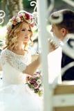 Sinnlig tryckande på emotionell lycklig blond brud för stilig brudgum in royaltyfri bild