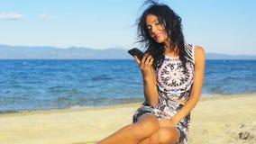 Sinnlig ung brunettkvinna på stranden som talar på hennes mobiltelefon lager videofilmer