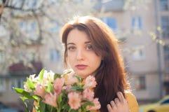 Sinnlig ung flicka som ser kameran och utomhus rymmer en stor bukett av färgrika blommor nära byggnaderna på arkivbilder